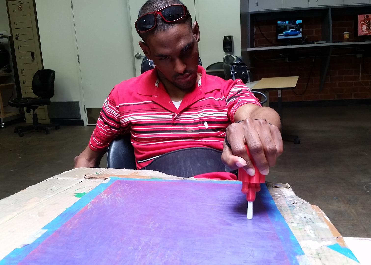 Derrick Gordon utilizing an adaptive palm grip tool.
