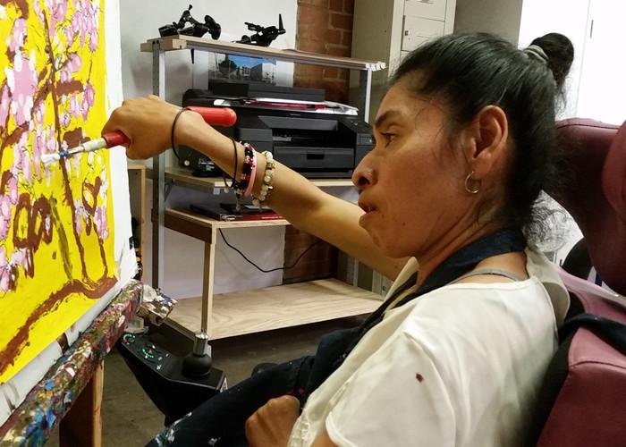 Lily Hernandez utilizing an adaptive grip tool.
