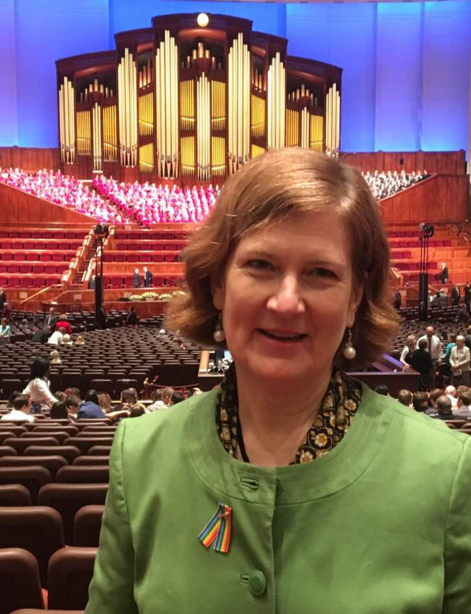 Erika is in a green jacket with a rainbow pin standing in the LDS Conference Center with the organ in the background.