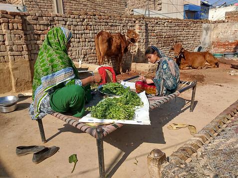 Een arm christelijke meisje maakt huiswerk terwijl haar moeder het eten voorbereid.