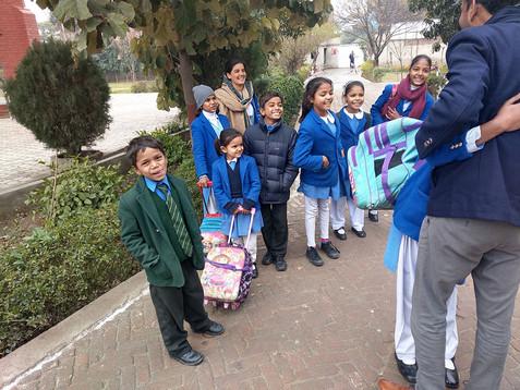 Een medewerker van Teach the Children haalt de kinderen op van school.