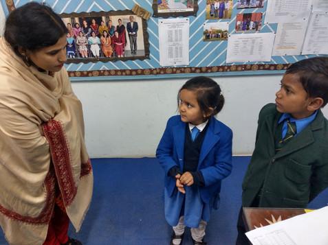 Een overhoring van de lerares. De kinderen worden getest over hun kennis van de bijbel.