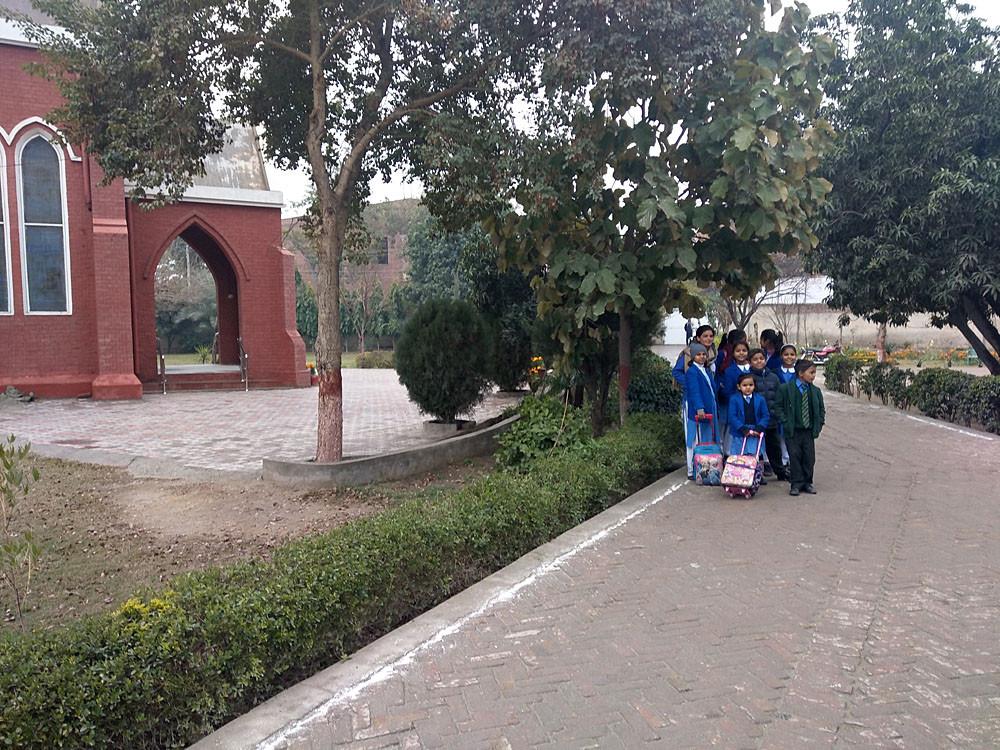 Kinderen van het Teach the Children project. Op het schoolterrein staat een grote kerk.