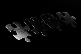 46618101-metal-puzzle-pieces-on-black-ba
