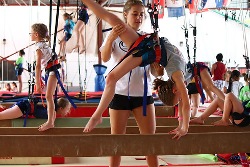 Camp de vacances de Gymnastique. Gymnaste sur poutre gymnova avec entraineur et ceinture acrobatique. Québec, Canada.