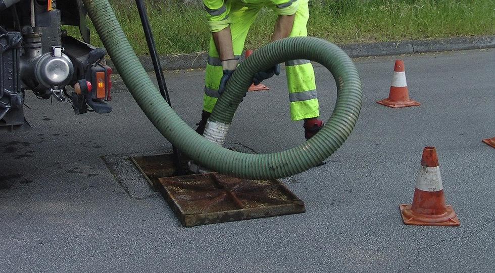Worker handling sewage pipe
