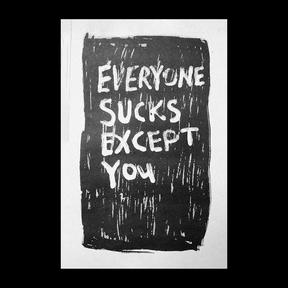A black and white poster with hand drawn letters saying EVERYONE SUCKS EXCEPT YOU