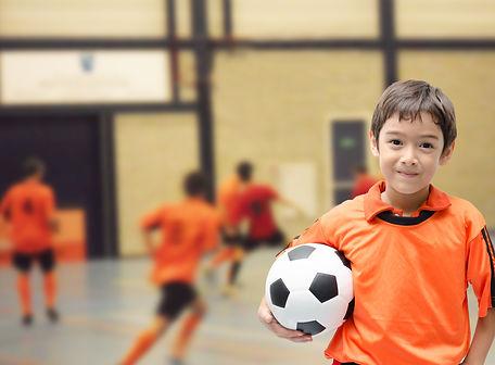 Little boy holding football soccer ball indoor gym.jpg
