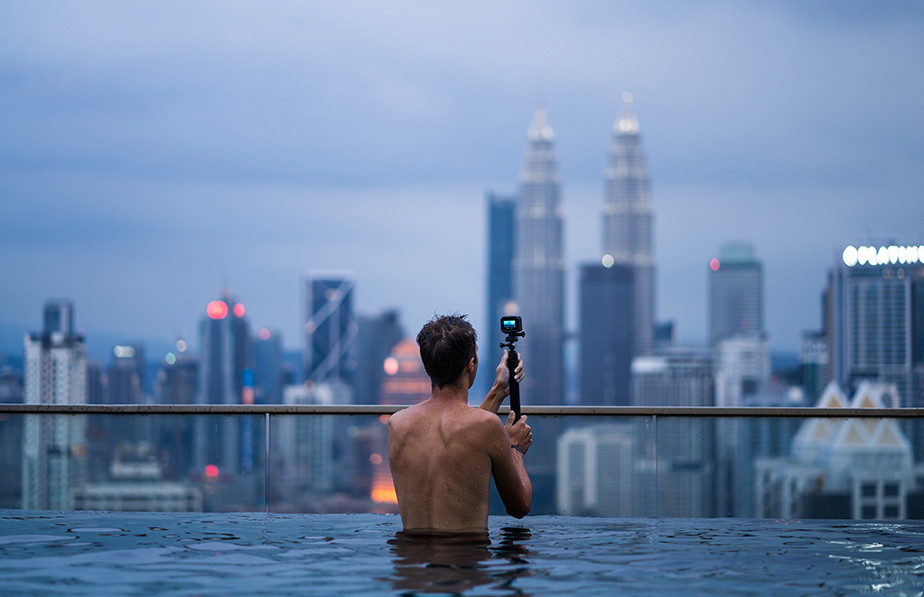 person using action camera on city pool