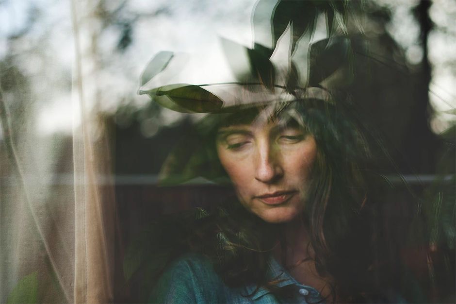 woman looking through the window with forest reflection