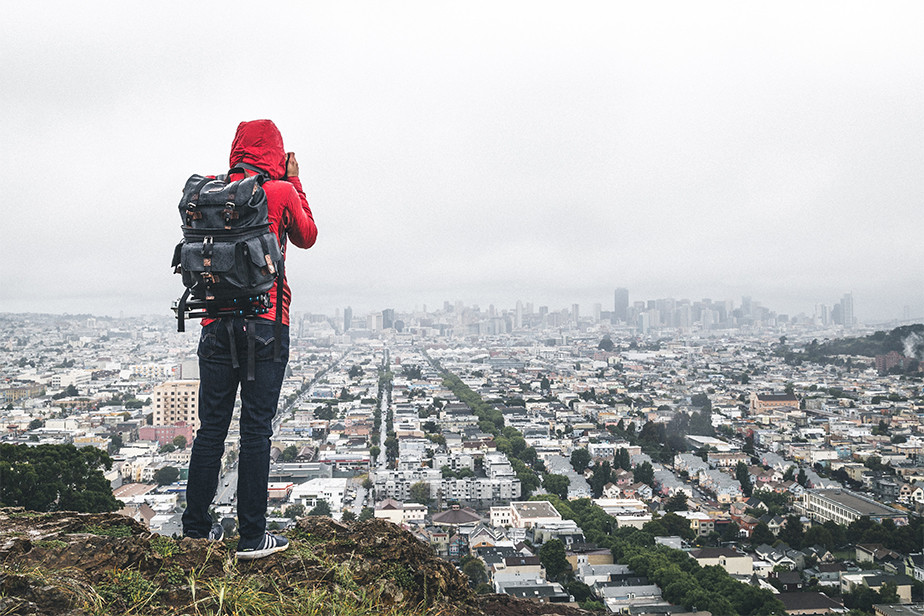 photographer with backpack standing on top of cliff to photograph city
