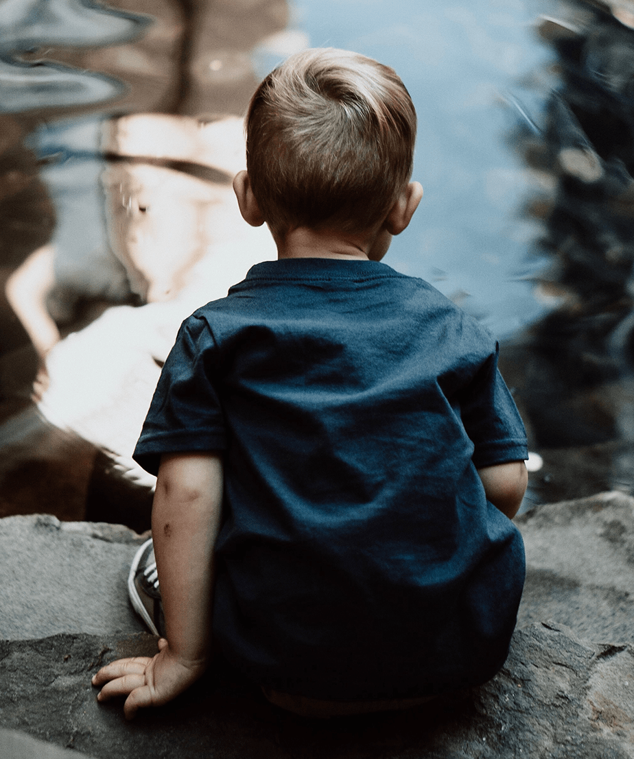 little blond boy sitting in front of pond