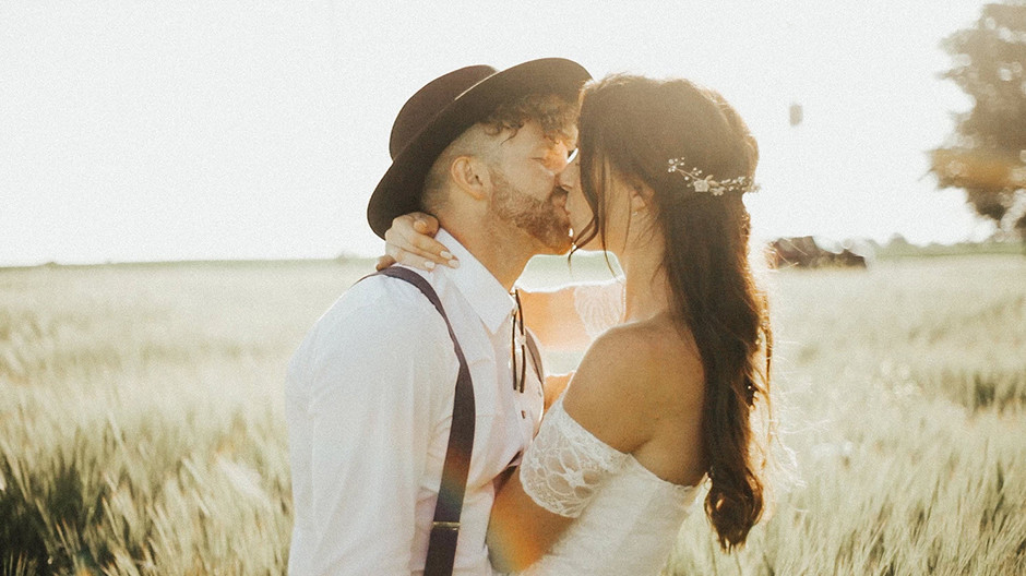 bride and groom couple kissing in a field