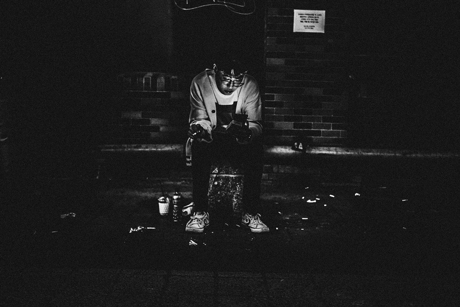 young man illuminated by phone light on dark street