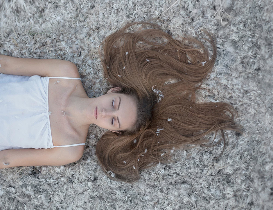 girl with long hair laying down on feathers