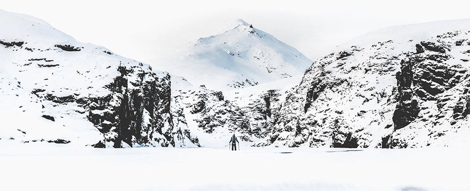 panorama of snowed mountains with person standing in the middle