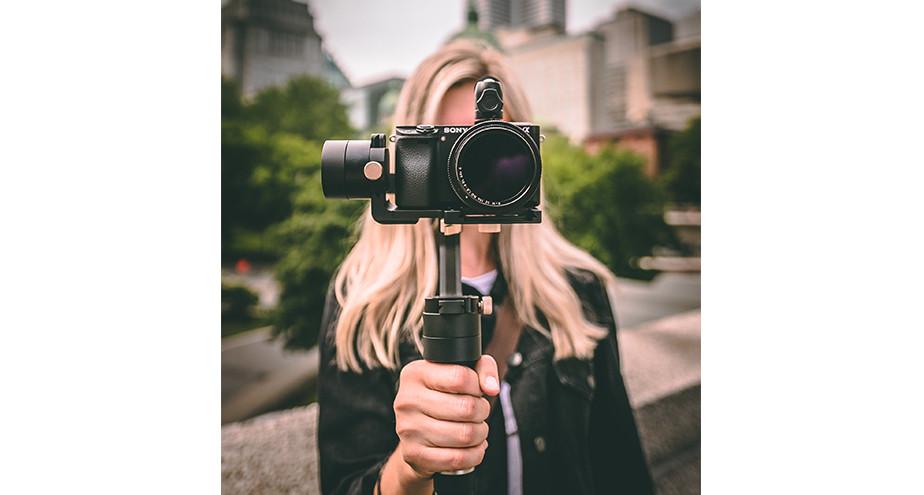 girl holding mirrorless camera on gimbal