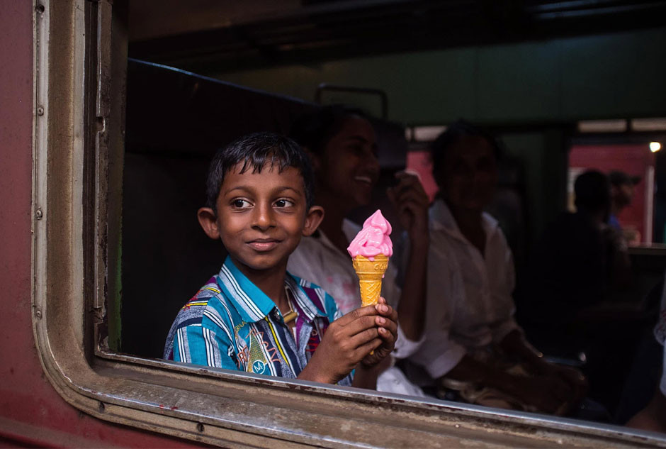 little indian boy eating ice cream on the train by Gaetan Haugeard