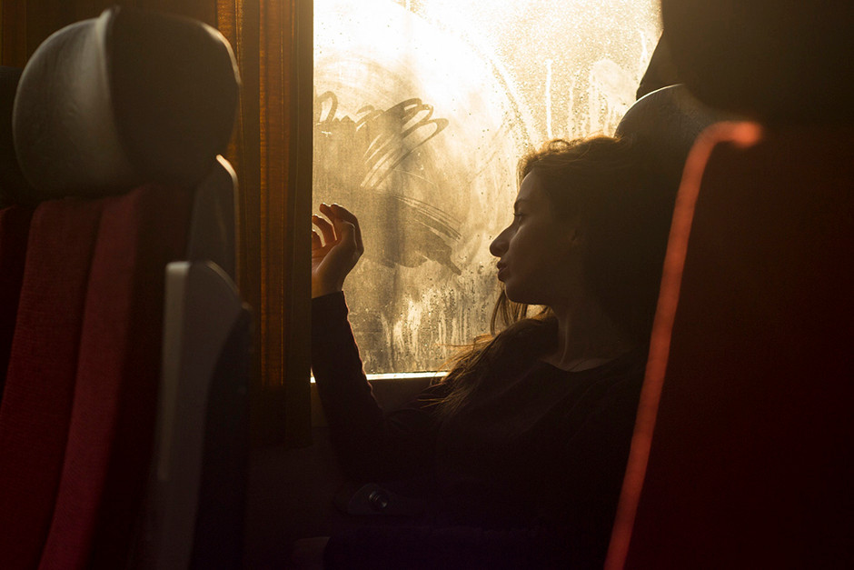 backlighting portrait of girl  looking out of bus window