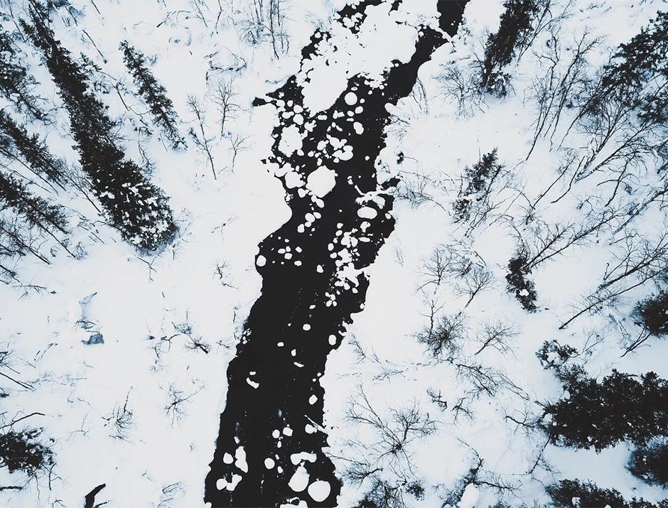monochrome drone landscape of dark river crossing snowed white forest