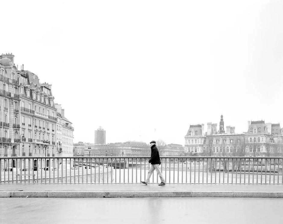 man crossing bridge over river in the city
