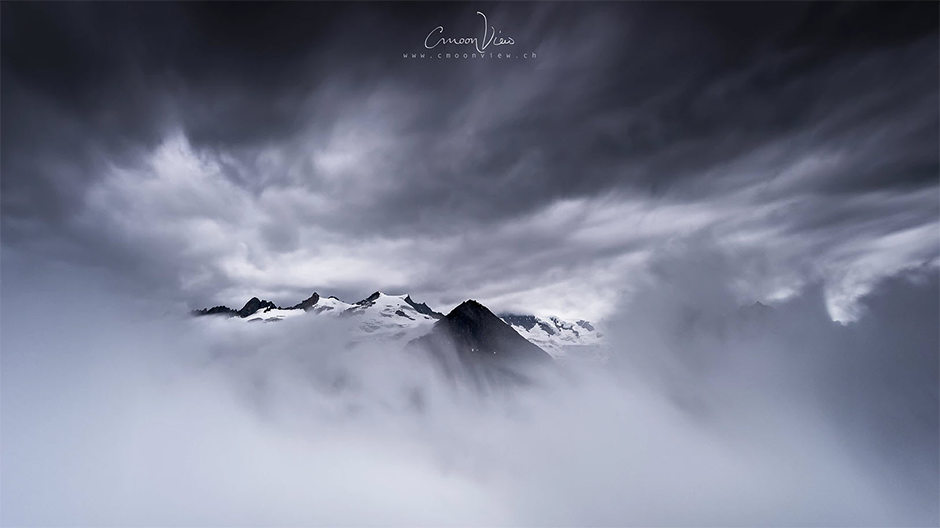 snowed mountain tops covered by clouds