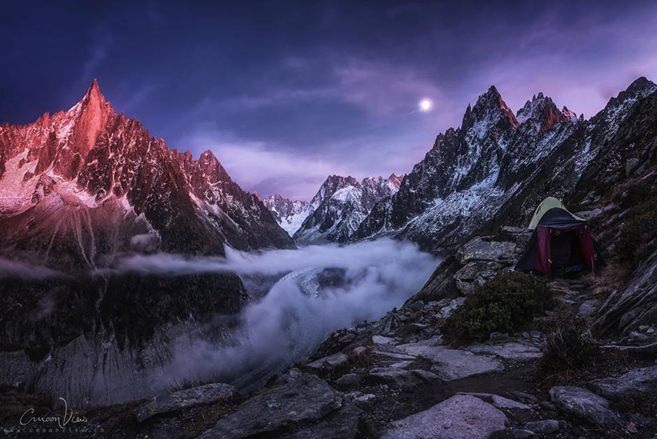 snowed and foggy mountain ridge at sunset