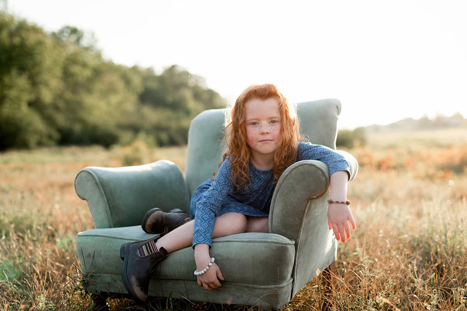 little red haired girl sitting on armchair in a field