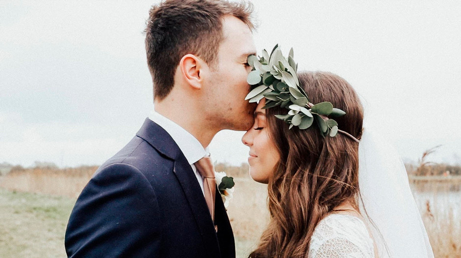 outdoor wedding photography groom kissing bride on the forehead