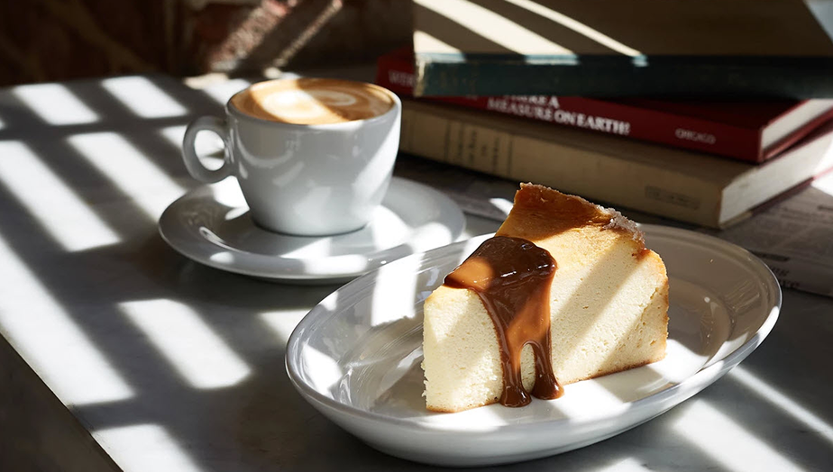 latte and cheesecake served on a table with books