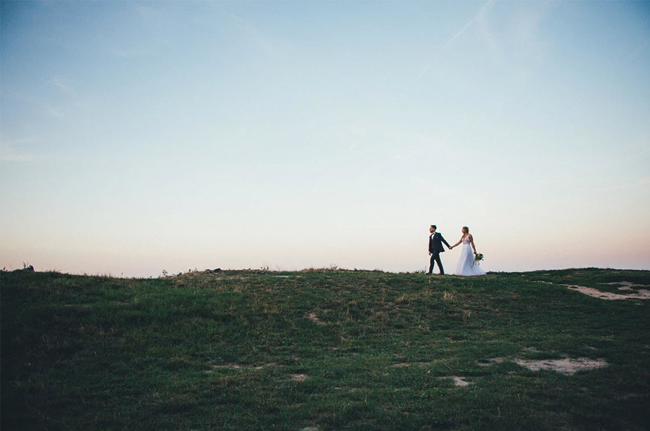 wedding photography couple walking on green field over blue sky
