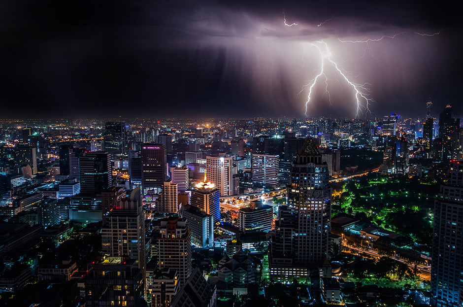 lighting storm falling over city at night