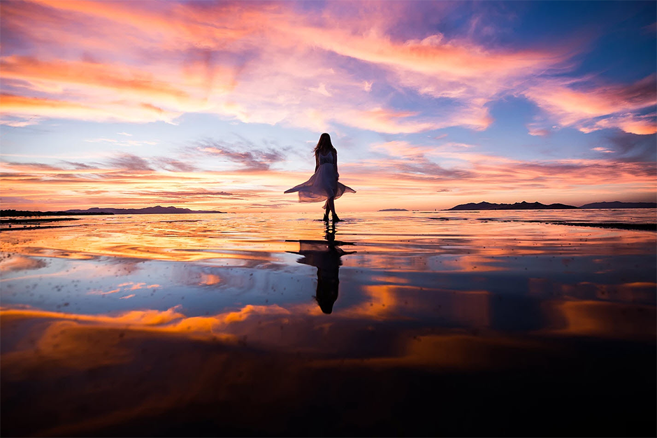 silhouette of girl with dress on the beach at sunset