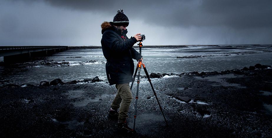 photographer using travel tripod on the beach