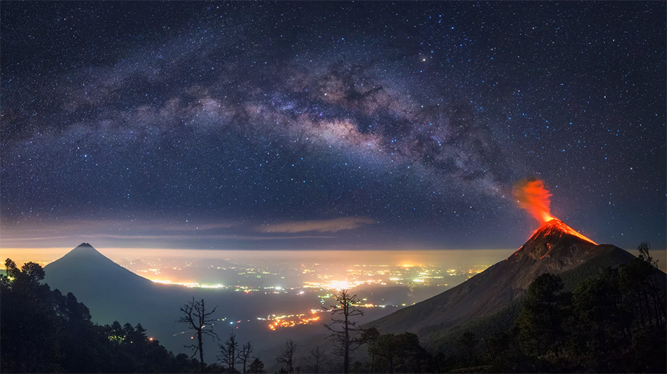 panoramic landscape photo of milky way over erupting volcano and city