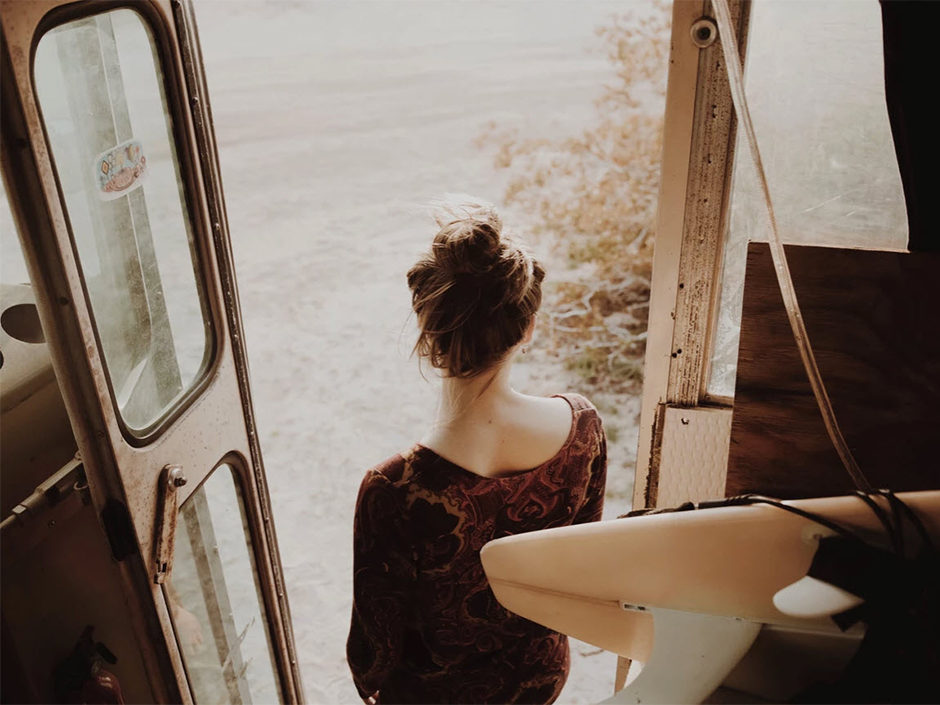 girl with hairbun in a van on the beach