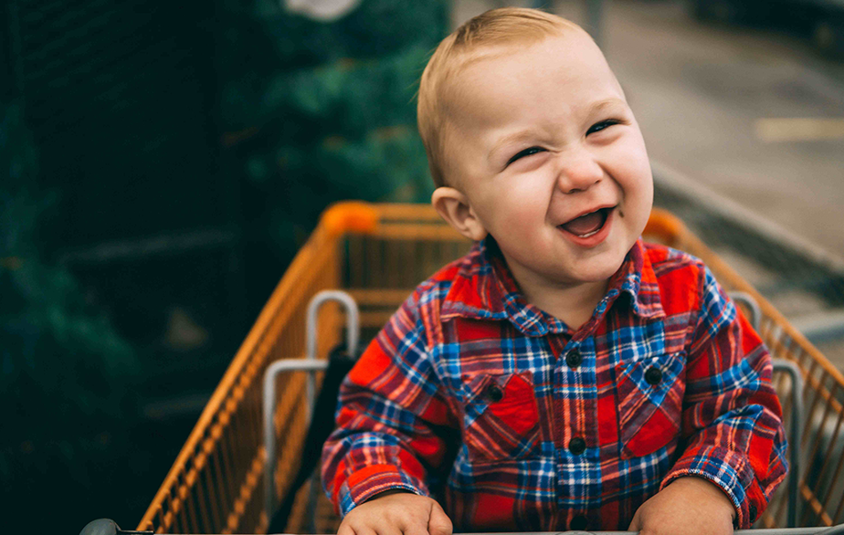 little blond boy sitting on a shopping cart and smiling