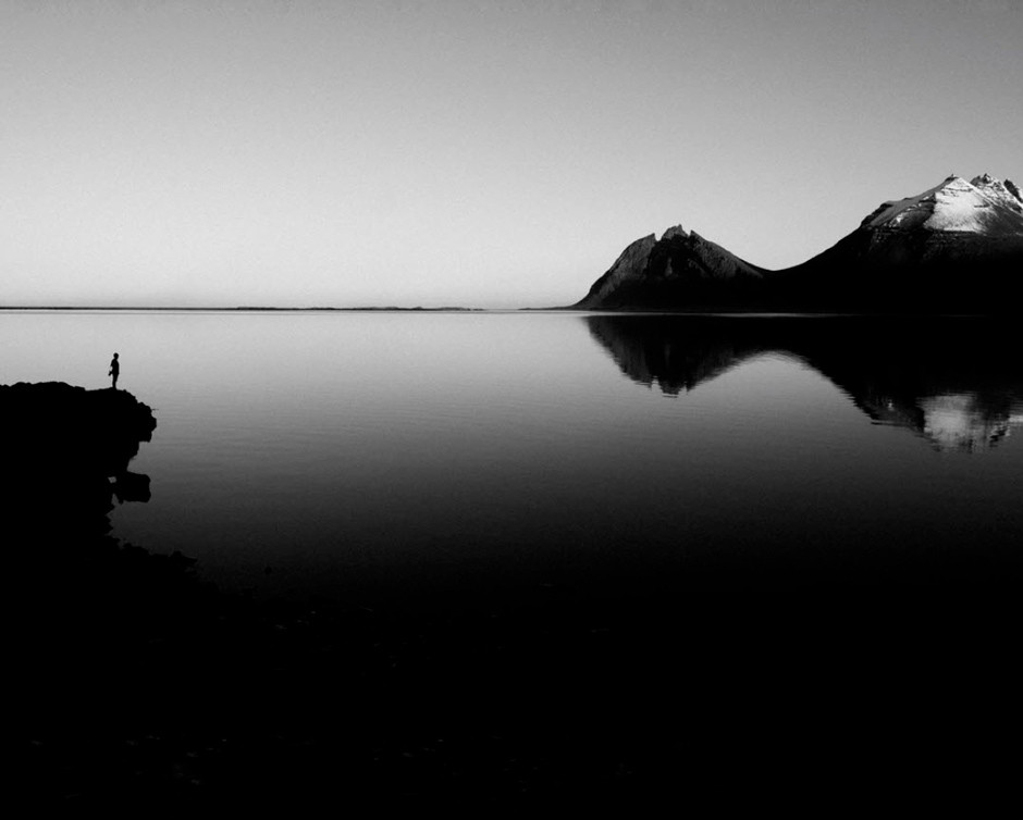 person standing at the edge of cliff overseeing mountain reflections on lake