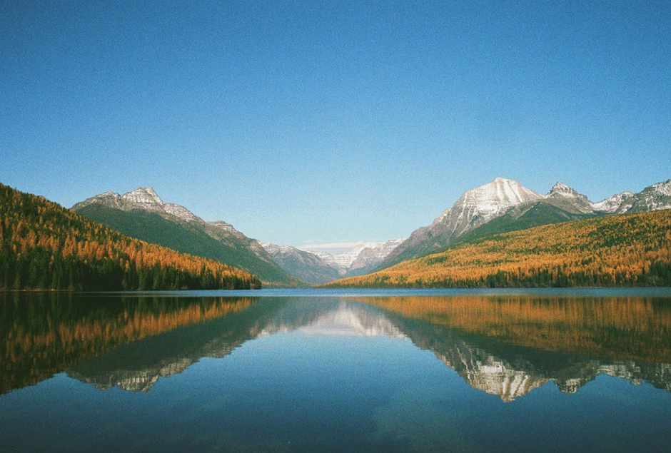 reflection of autumn forest and snowed mountains over lake