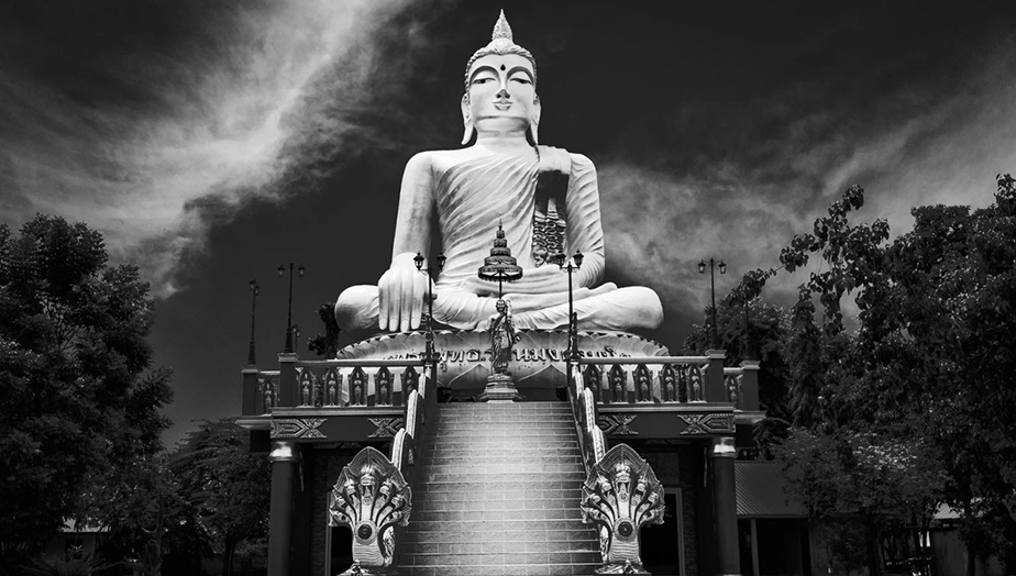 black and white photo of huge buda statue on top of stairs