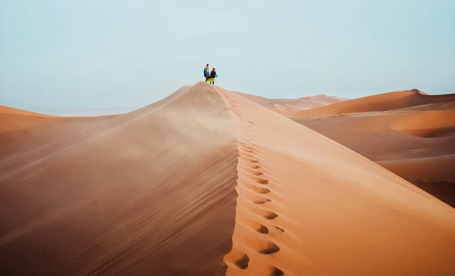 couple standing on sand dune
