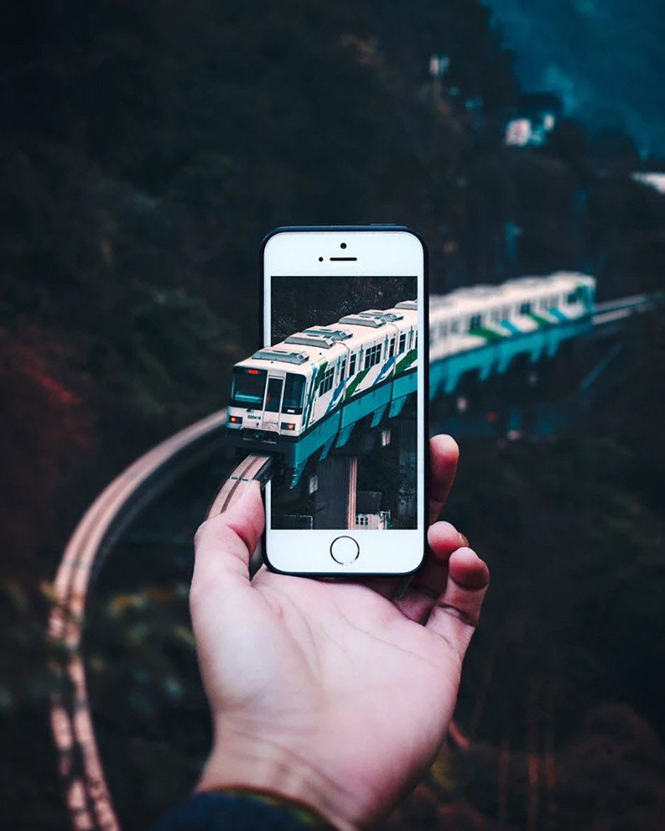 surreal composition train passing phone screen for photography inspiration