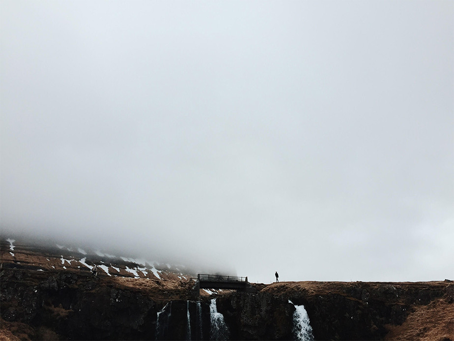 person walking above waterfalls on foggy mountain
