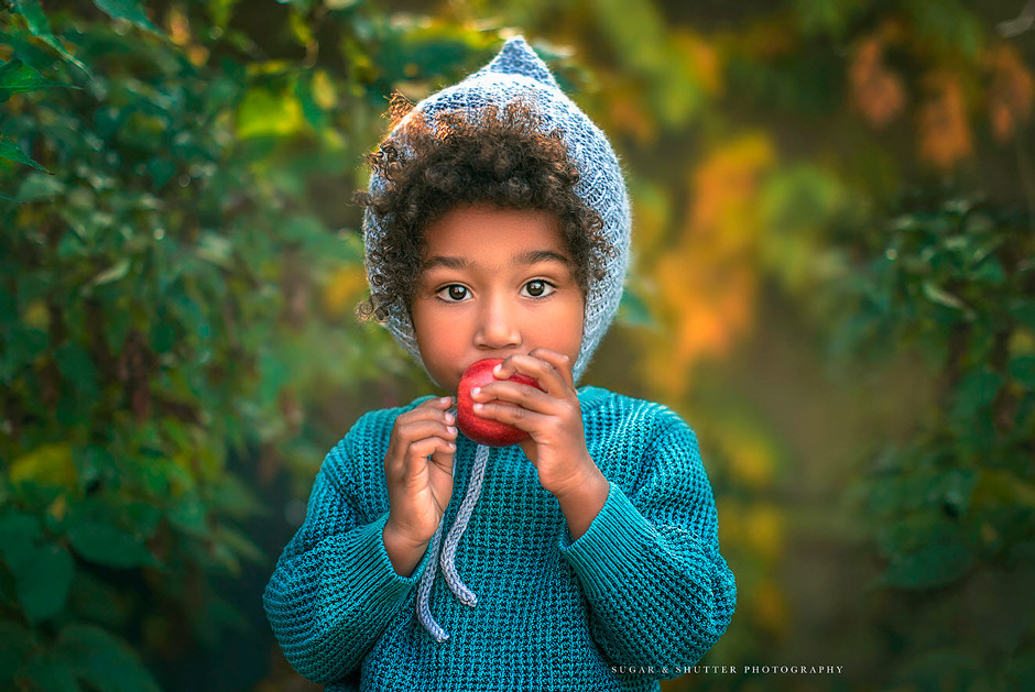 potrait photography little boy eating an apple in the forest