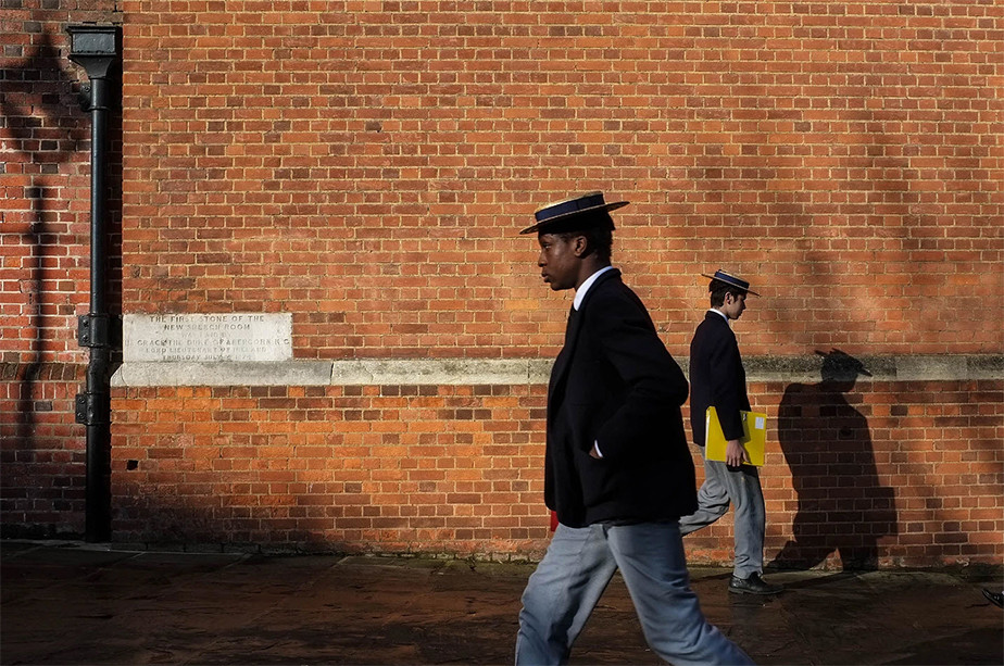 street photography uniformed school kids passing each other in front of brick wall