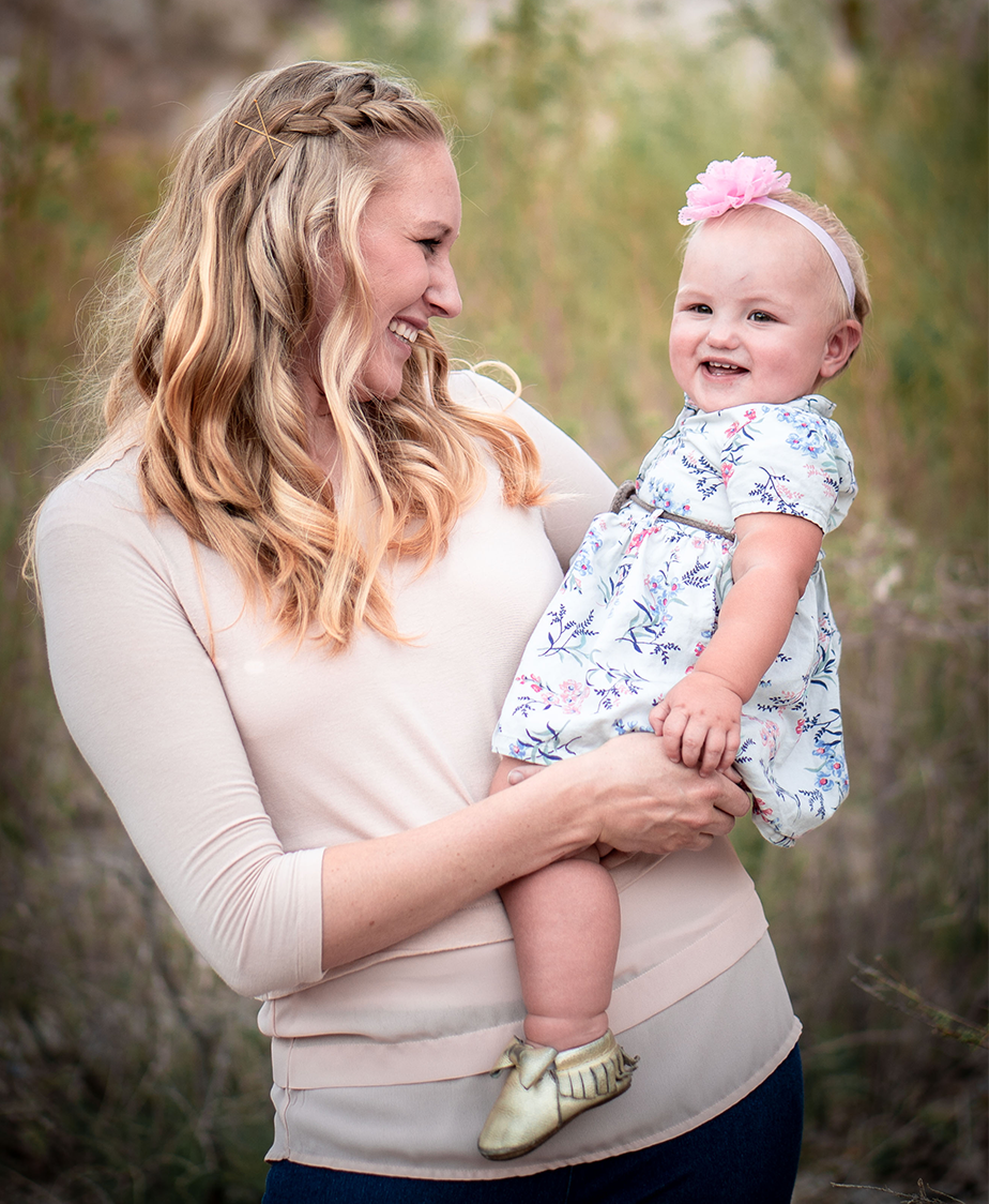 blonde woman holding a toddler on her hip