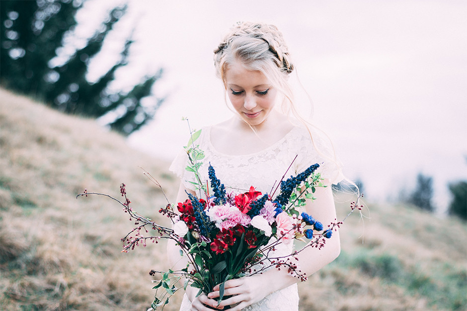 bride standing on a field and holding a bouquet of wild colorful flowers