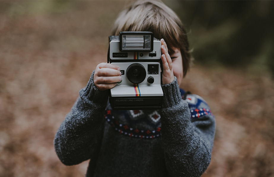 boy holding instant polaroid camera