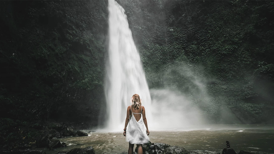 blonde girl with white dress standing in front of a waterfall