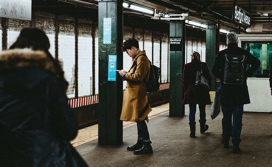 guy looking at smartphone on subway station